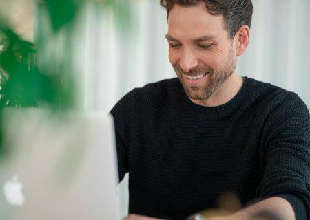 Lachender Mann arbeitet am Laptop
